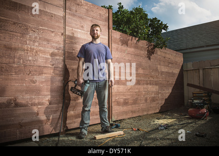 Portrait of joiner in backyard in front of new fence - Stock Photo