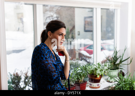 Young woman in sitting room holding cellphone - Stock Photo