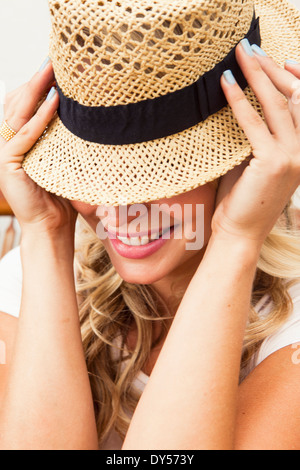 Young woman putting on straw hat