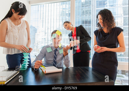 Female office workers covering male colleague with sticky notes - Stock Photo