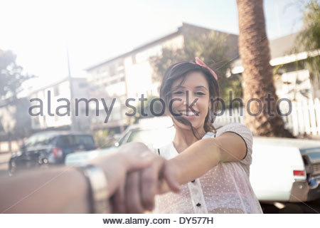 Young woman holding boyfriends hand on suburban street - Stock Photo