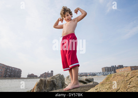 Boy at the coast showing off his arm muscles, Long Beach, New York State, USA - Stock Photo
