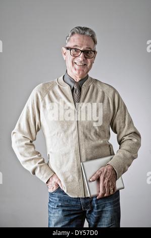 Portrait of senior man, hand in pocket, holding bag - Stock Photo