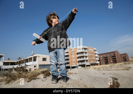 Boy at the coast preparing to fly toy airplane, Long Beach, New York State, USA - Stock Photo