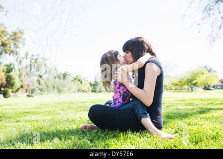 Mid adult woman and young daughter sitting in park - Stock Photo