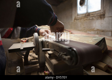 Close up of mature man using sanding belt in workshop - Stock Photo