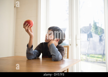 Boy sitting at table, holding an apple in front of him - Stock Photo