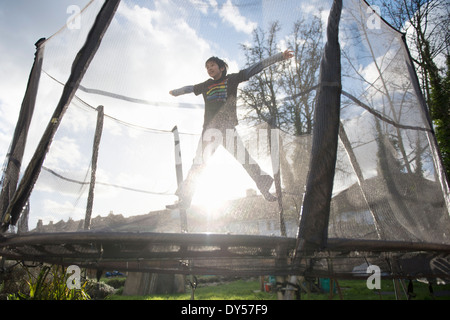 Boy jumping on outdoor trampoline - Stock Photo