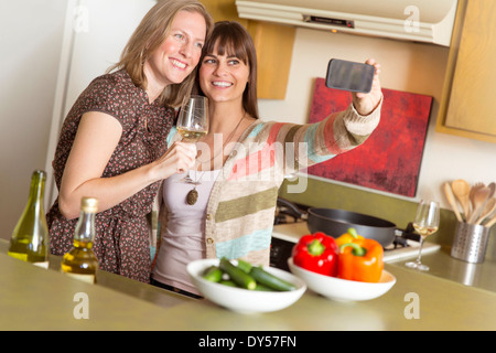 Mid adult female friends taking self portrait on smartphone in kitchen - Stock Photo