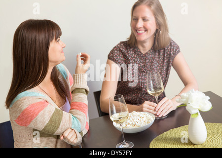 Mid adult female friends drinking white wine and eating popcorn - Stock Photo