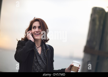 Young woman with cellphone and coffee next to Hudson river, New York, USA - Stock Photo
