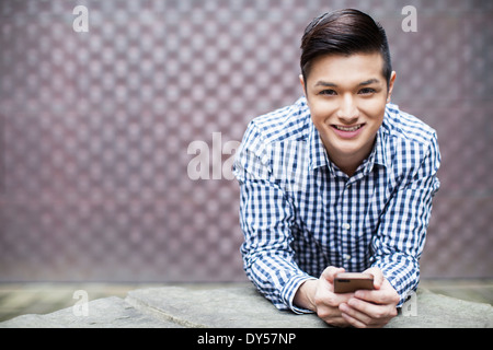 Portrait of young man holding smartphone - Stock Photo