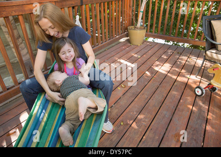 Mother and children playing on hammock - Stock Photo