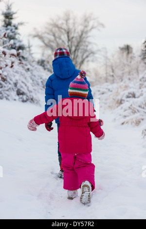 Brother and sister walking in snow - Stock Photo