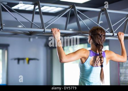 Young woman doing chin ups - Stock Photo