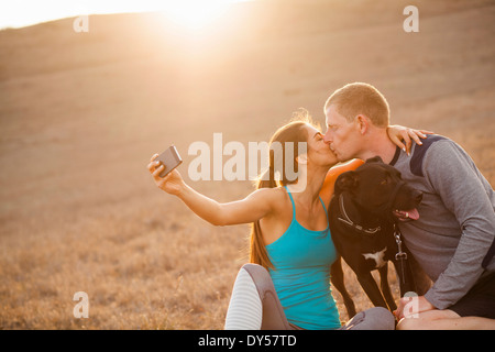 Kissing couple with dog - Stock Photo