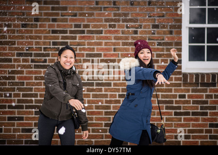 Two you adult females throwing snowballs - Stock Photo