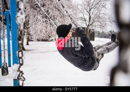 Young man playing on park swing at -30 degrees celcius - Stock Photo