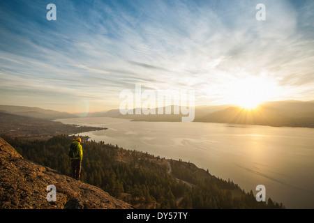 Male hiker watching sunset over Okanagan Lake, Naramata, British Columbia, Canada - Stock Photo