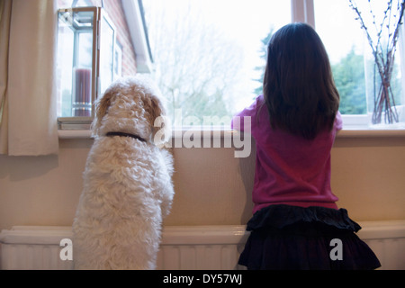 Girl and her pet dog standing and looking out of window - Stock Photo