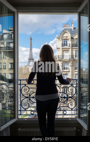 Woman looking at the Eiffel Tower, Paris, France, viewed through an open window. - Stock Photo