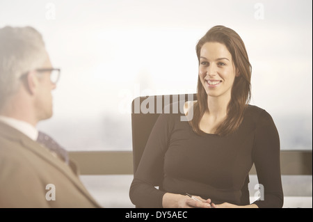 Business colleagues chatting at desk in office - Stock Photo
