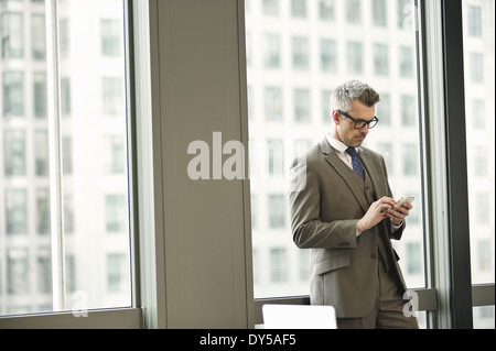 Businessman texting on smartphone in office - Stock Photo