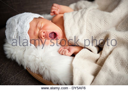Portrait of newborn baby girl yawning - Stock Photo