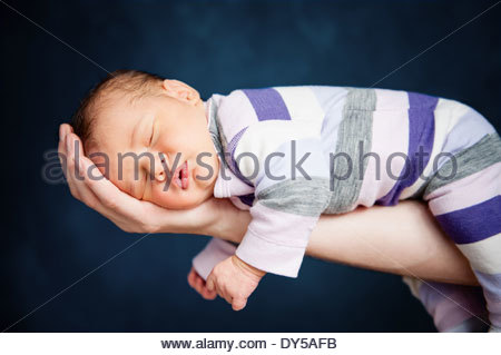 Portrait of newborn baby girl lying on father's arm - Stock Photo