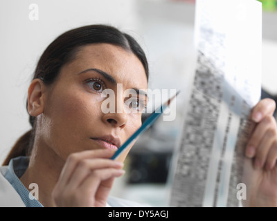 Female scientist examining DNA gel in laboratory for genetic research - Stock Photo