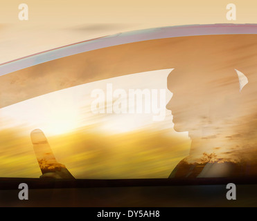 Silhouette of woman driving car - Stock Photo