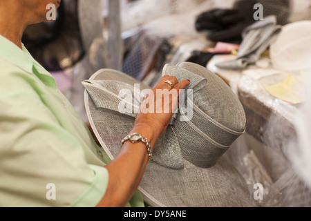 Senior woman holding hat in traditional milliners shop - Stock Photo