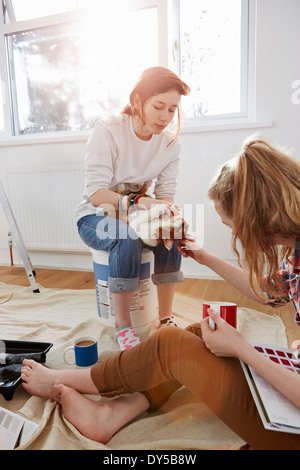 Two teenage sisters with color swatches, coffee and a cat - Stock Photo