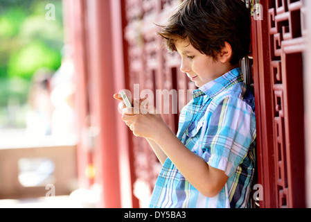 Boy leaning against red door texting on cellphone - Stock Photo