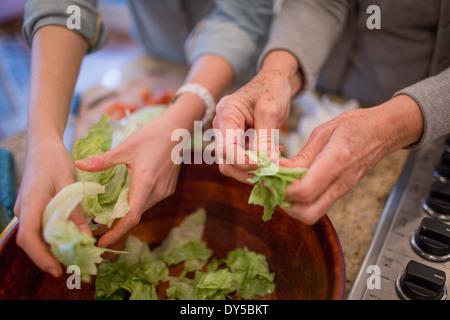 Senior woman and granddaughter preparing lettuce for salad - Stock Photo