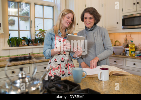 Senior woman and granddaughter checking recipe on digital tablet - Stock Photo