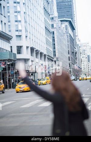 Young woman hailing a yellow cab, New York, USA - Stock Photo