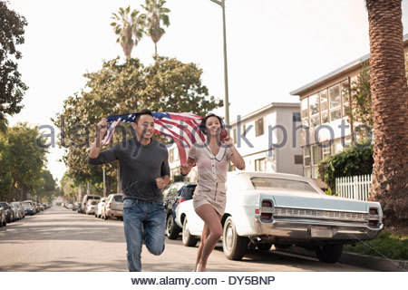 Couple running along street with the American flag - Stock Photo