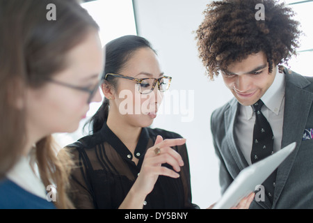 Three colleagues using digital tablet - Stock Photo