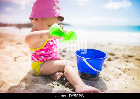Baby playing on sandy beach with bucket and spade - Stock Photo