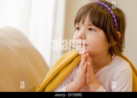 Young girl sitting on sofa daydreaming