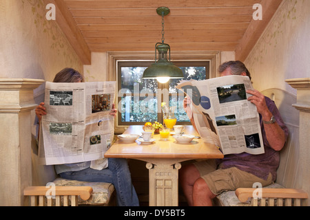 Couple at breakfast table, ignoring each other, reading newspapers - Stock Photo