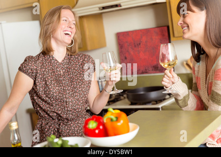 Mid adult female friends drinking wine and laughing in kitchen - Stock Photo