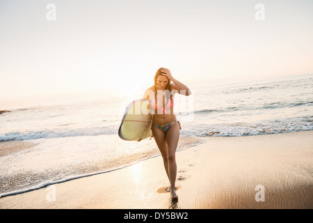 Surfer carrying surf board, out of sea - Stock Photo