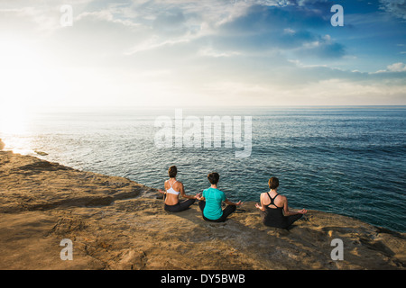 Women sitting on cliff top, looking at sea and meditating - Stock Photo