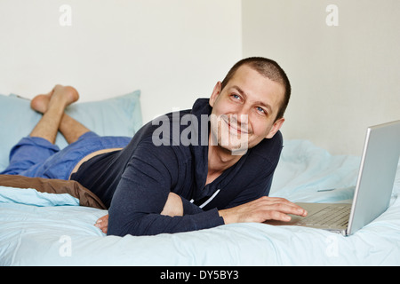 Mid adult man lying on bed using laptop - Stock Photo