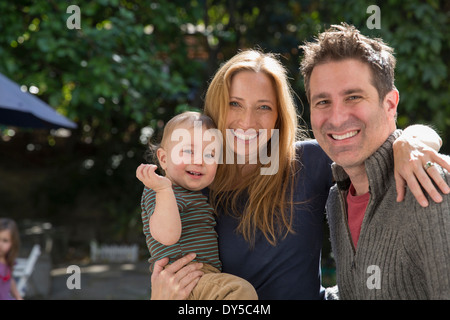 Father and mother with baby in garden - Stock Photo