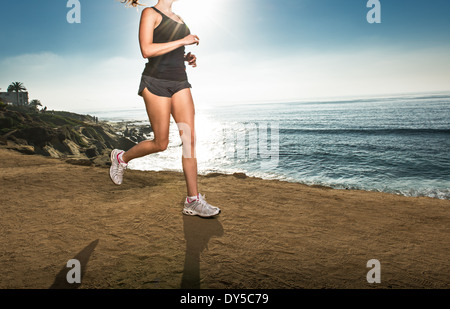 Mid adult woman jogging along cliff - Stock Photo