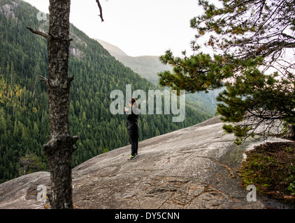 Young woman looking at smartphone, Squamish, British Columbia, Canada - Stock Photo