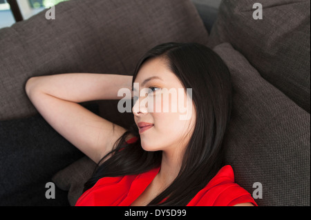 Portrait of young woman daydreaming on sofa - Stock Photo